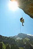 Young man rappelling, Gimmelwald, Lauterbrunnen, Canton Bern, Switzerland
