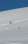 Hang glider and skier at Lake Falkertsee, Carinthia, Austria