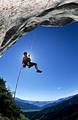 Rock climber rapelling down from an overhang of the summit of Kampenwand, view towards Tyrol, Chiemgau, Upper Bavaria, Bavaria, Germany