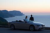Couple with car on coastal road, North Coast, Majorca, Spain