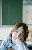 Bored boy sitting in classroom, portrait