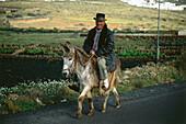 Farmer riding on donkey, La Vegueta, Lanzarote, Canary Islands, Spain