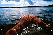 Man swimming in lake, close-up hands, Vastergotland, Sweden