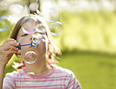 Girl (7-8 years) blowing soap bubbles