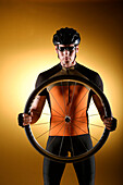 Male cyclist holding a wheel
