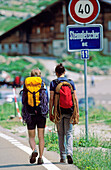 Two young women with climbing equipment walking along street, Bernese Oberland, Canton Bern, Switzerland, MR