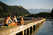 Young people sunbathing on boardwalk, Castle Landskron in background, Lake Ossiach, Ossiach, Carinthia, Austria