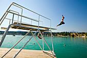 Boy jumping from diving platform into Worthersee, Hotel Schloss Velden in background, Velden, Carinthia, Austria