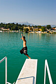 Boy jumping from diving platform into Wörthersee (biggest lake of Carinthia), Hotel Schloss Velden (served as the location for the TV series Ein Schloss am Wörthersee) in background, Strandbad, Velden, Carinthia, Austria