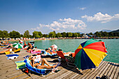 Young people sunbathing on landing stage at Strandbad Klagenfurt, Lake Wörthersee (biggest lake of Carinthia), Klagenfurt, Carinthia, Austria