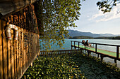 Two people sitting on a landing stage near a boat house at Lake Faak, Carinthia, Austria