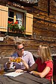 Couple clinking glasses, Lammersdorfer Hut, 1650 m, Lammersdorf near Millstatt, Carinthia, Austria