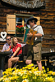 Couple listening to musician playing the accordion, Steirische Accordion, Lammersdorfer Hut, 1650 m, Lammersdorf near Millstatt, Carinthia, Austria