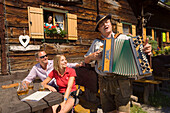 People listening to man playing accordion, Lammersdorf hut, Lammersdorf near Millstatt, Carinthia, Austria