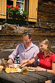 Couple eating a snack at Lammersdorfer hut 1650 m, Lammersdorf near Millstatt, Carinthia, Austria