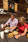 Couple eating Kaiserschmarrn, sugared pancake with raisins, Lammersdorfer Hut, 1650 m, Lammersdorf near Millstatt, Carinthia, Austria