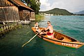 Young couple in a rowing boat on Lake Faak near a boathouse, Carinthia, Austria