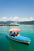 Excursion ship at landing stage of Maria Wörth, family in an electric powered boat in foreground, Lake Wörthersee (biggest lake of Carinthia), Maria Wörth, Carinthia, Austria