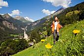 Woman hiking over alp above Heiligenblut with pilgrimage church Zum heiligen Blut, view to Grossglockner, Heiligenblut, Carinthia, Austria