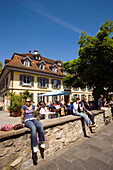 Young people sitting on wall, restaurant in background, Thun (largest garrison town of Switzerland), Bernese Oberland (highlands), Canton of Bern, Switzerland