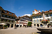 Fountain, cyclist passing Rathausplatz (town hall square), Castle Thun in background, Thun (largest garrison town of Switzerland), Bernese Oberland (highlands), Canton of Bern, Switzerland