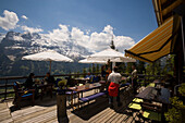 People sitting on terrace of the mountain restaurant Aellfluh, Grindelwald, Bernese Oberland (highlands), Canton of Bern, Switzerland