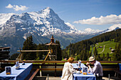 Couple sitting on terrace of the mountain restaurant Berghaus Bort (1600 m), First, Eiger (3970 m) in background, Grindelwald, Bernese Oberland (highlands), Canton of Bern, Switzerland