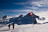Two people hiking at Jungfraufirn glacier, passing a Swiss flag, Grindelwald, Bernese Oberland, Canton of Bern, Switzerland
