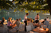 Waiters taking order for guests in the open air area of a restaurant, Lake Fuschl, Fuschl am See, Salzkammergut, Salzburg, Austria