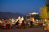 People sitting on terrace of the restaurant Mönchsberg 32 in the evening, view over old town with Hohensalzburg Fortress, Salzburg, Salzburg, Austria, Since 1996 historic centre of the city part of the UNESCO World Heritage Site