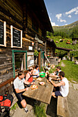 Group of hikers eating a Jause (snack) at Rastötzen Alm (1743 m), Bad Hofgastein, Gastein Valley, Salzburg, Austria