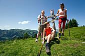 Three hikers resting at sign post, Bichlalm (1731 m), Grossarl Valley, Salzburg, Austria