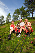 Three hikers having a break at meadow with blooming alpine roses, Grossarl Valley, Salzburg, Austria