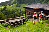 Couple arriving Karseggalm (1603 m, one of the oldest mountain hut in the valley), Grossarl Valley, Salzburg, Austria