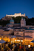 View over illuminated roof deck of restaurant Hotel Stein to old town with Salzburg Cathedral and  Hohensalzburg Fortress, largest, fully-preserved fortress in central Europe, in the evening, Salzburg, Salzburg, Austria, Since 1996 historic centre of the