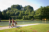 People strolling through Hellbrunn Park, Month Palace in background, Hellbrunn Palace, oldest baroque palace site north of the Alps, Salzburg, Salzburg, Austria