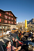 Hikers resting on the terrace of the Alpine hut Fluhalp, Zermatt, Valais, Switzerland
