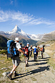 Group of hikers arriving the mountain village Findeln, Matterhorn (4478 m) in background, Zermatt, Valais, Switzerland