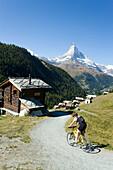Female mountainbiker arriving the mountain village Findeln, Matterhorn (4478 m) in background, Zermatt, Valais, Switzerland