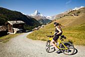 Female mountain biker looking towards the mountain village Findeln, Matterhorn, 4478 m, in the background, Zermatt, Valais, Switzerland