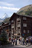 Tourists walking over Bahnhofplatz, Matterhorn (4478 m) in background, Zermatt village, Zermatt, Valais, Switzerland