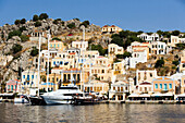 Yacht and sailing boats anchoring at quay of harbour Gialos, picturesque mansions at mountainside in background, Simi, Symi Island, Greece