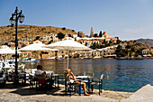 People sitting in pavement cafe and looking over the harbour Gialos to monastery Moni Evangelismos, Simi, Symi Island, Greece