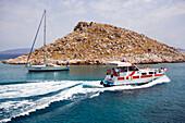 Taxi boat and sailing boat in bay near Agia Marina Beach, Pedi, Symi Island, Greece