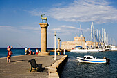 Columns with deer and doe (Elafos and Elafia) at port entrance of the Mandraki harbour (translated literally: fold), fortress tower Agios Nikolaos in background, Rhodes Town, Rhodes, Greece