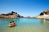 Mother and children bathing in the Saint Paul's Bay (Agios Pavlos), Lindos, Rhodes, Greece
