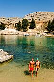 Couple walking through water of the Saint Paul's Bay (Agios Pavlos), Lindos, Rhodes, Greece
