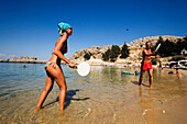 Couple playing beach pingpong, standing in shallow water, Saint Paul's Bay (Agios Pavlos), Lindos, Rhodes, Greece