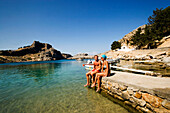 Couple sitting on rocks and talking, Saint Paul's Bay (Agios Pavlos), Acropolis in the back, Lindos, Rhodes, Greece