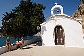 Couple sitting in front of Saint Paul's Chapel, Saint Paul's Bay (Agios Pavlos), Lindos, Rhodes, Greece